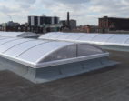 Vertical End dome end skylights on a flat roof with a city view