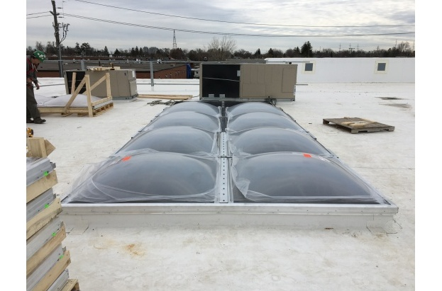 Bronze Acrylic Dome Butted Skylights on a White Reflective Roof
